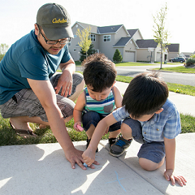 A family playing with chalk on a driveway.